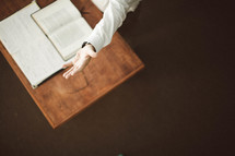 Left hand raised over open Bible on wooden desk.