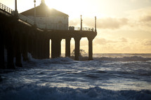Church on a pier with waves crashing beneath it at sunset.