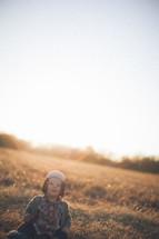 Toddler child sitting on grassy hill at sunrise.
