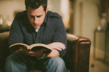 man sitting reading a Bible