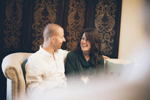 couple smiling at each other sitting on a couch