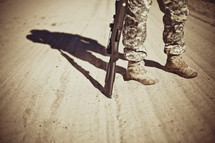 A soldier standing on a dirt road with a rifle.