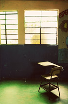 An solitary empty desk in a classroom