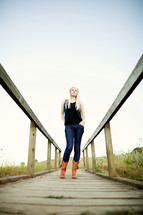 Young woman standing on a wood board walk boots fashion