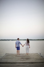 a couple holding hand standing at the edge of a pier