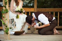 groom washing and kissing the feet of his bride - foot washing ceremony