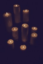 A collection of lit candles isolated on black
