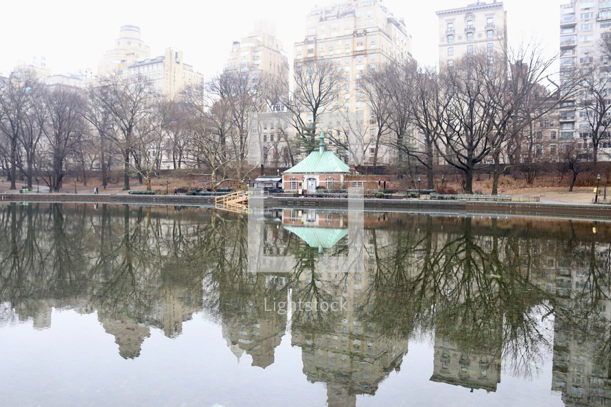 reflection of city buildings on pond water