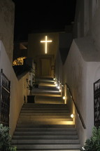 illuminated cross at the top of a stairway
