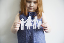 A little girl holds a paper cutout of a family.
