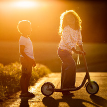 kids in warm sunlight with a scooter