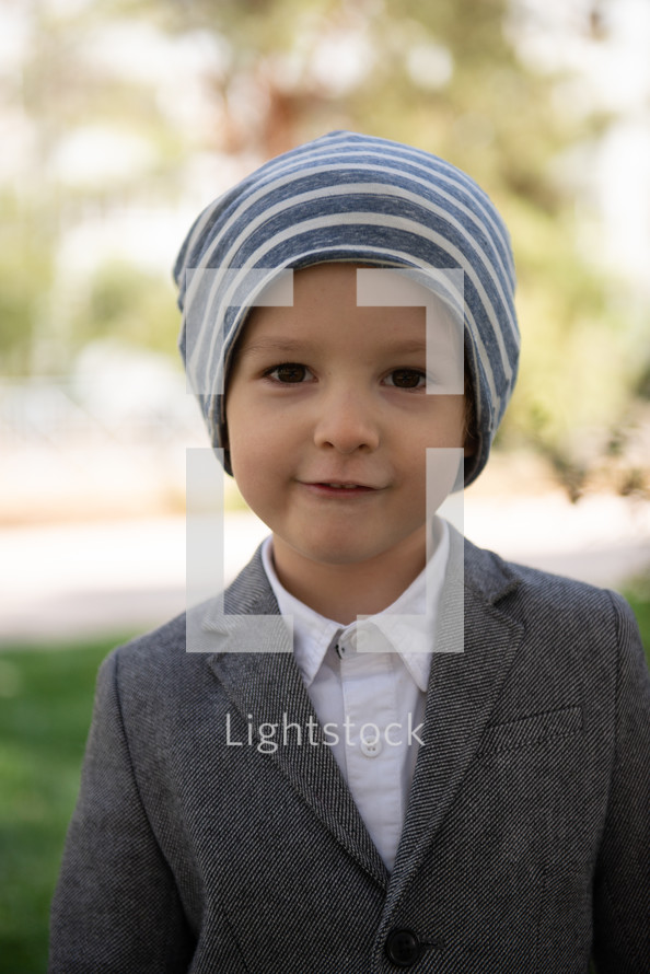 portrait of a boy in dress clothes and knit cap