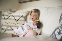 an infant and toddler girl on a couch