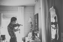 a teenage boy playing a fiddle in a mirror