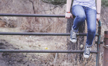 young woman sitting on a metal gate