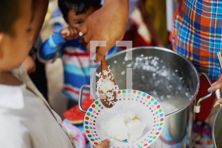 serving rice to hungry children