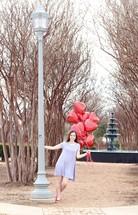teen girl holding heart shaped helium balloons