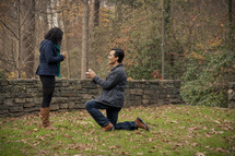 man on one knee proposing to a woman outdoors