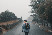 a man walking on a paved path