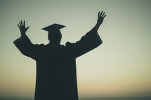 silhouette of a graduate with his hands raised