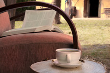 tea cup and open Bible in a chair outdoors