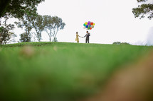 a distant couple holding helium balloons