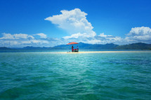 couple with an umbrella on a sand bar in tropical water