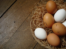 Natural eggs in a basket on a wooden floor.