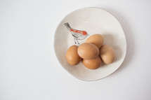 Brown eggs on a white plate with a drawing of a bird.