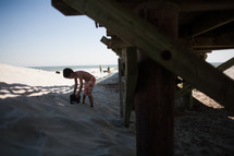 a boy child playing in the sand on a beach near a pier
