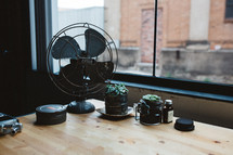 fan and house plants on a desk