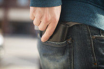a man putting a wallet in his back pocket
