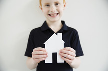 A smiling boy holding a paper cut-out of a house.
