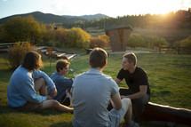 young men sitting outdoors talking at sunset