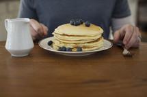 man eating a stack of pancakes