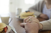 couple holding hands in prayer before breakfast.