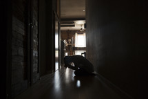 a woman sitting in a dark hallway covering her face