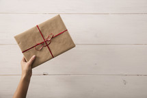 A gift wrapped in brown paper with a red ribbon being placed on a table.