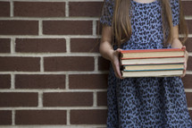 a girl holding a stack of books