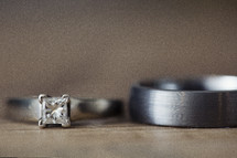 close up of wedding rings laying next to one another on a wood table.