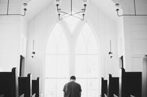 a man kneeling in prayer at the alter