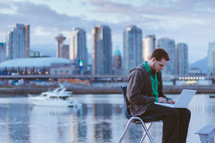 Man sitting on a chair with his laptop near and ocean bay by a city skyline.
