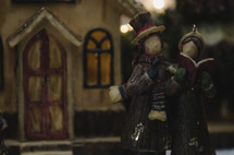 carolers in a Christmas village