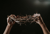 holding up a crown of thorns