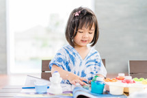 little girl painting with paints