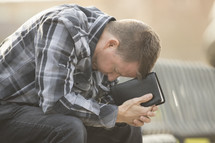 a man with his head down leaning on a Bible
