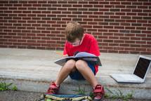 a boy doing his homework sitting on a curb