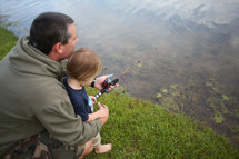 father and son fishing at a pond