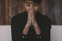 A young man praying with his hands pressed together.