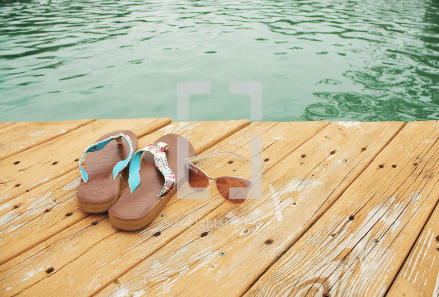 flip flops and sunglasses on a wood dock